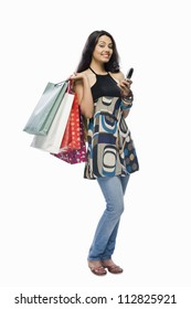 Portrait of a young woman holding shopping bags and a mobile phone