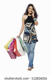 Portrait of a young woman holding shopping bags and talking on a mobile phone