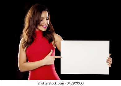 Portrait of young woman holding sign card over a black background.