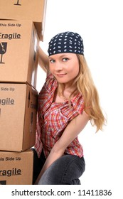 Portrait of a young woman holding a stack of cardboard boxes.