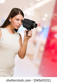 Portrait Of A Young Woman Holding Video Camera, indoor