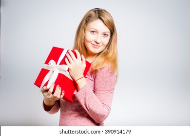 Portrait of a young woman holding a wrapped gift, isolated on a gray background