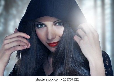 Portrait of a young woman in hood over forest background