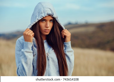 Portrait of a young woman in hoodie in the nature