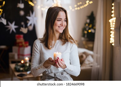 Portrait of young woman indoors at home at Christmas, holding candle.