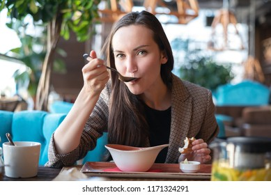 Portrait of a young woman in the interior of the restaurant at the table eating soup with bread, blurred background.