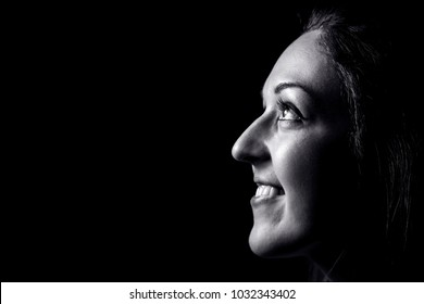 Portrait of young woman isolated on black background, close up.
