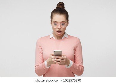 Portrait of young woman isolated on gray background, looking agitated at display of her smartphone, impressed by media content from web