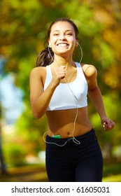 portrait of a young woman jogging and listening to the player