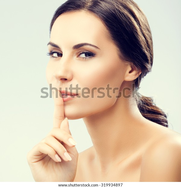 Portrait of young woman keeping finger on her lips and asking to keep quiet