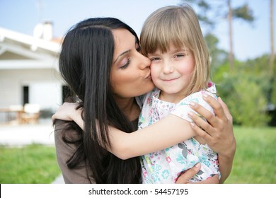 Portrait of a young woman kissing a little girl on the cheek