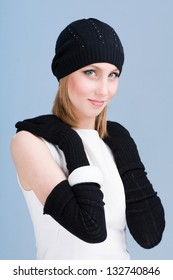 portrait of a young woman in knit wool hat and mittens. Isolated on blue background
