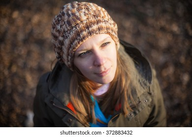 Portrait of young woman in knitted cap at city park