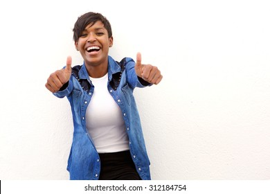 Portrait of a young woman laughing with thumbs up sign