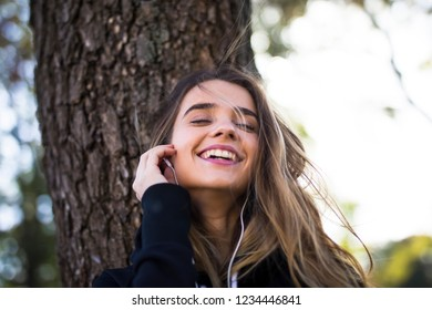 Portrait of young woman listening music outdoor by the tree