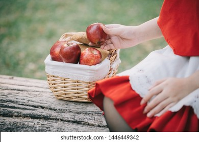 Portrait young woman with Little Red Riding Hood costume with apple and bread on basket sitting in green tree park background