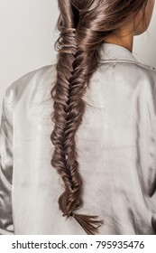 Portrait of young woman with a long braided pigtail, dressed in a metallic colored bomber jacket, back view