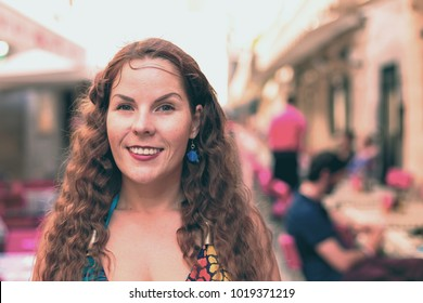 Portrait of young woman with long curly hair. Street photo outdoor