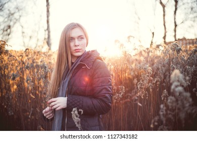 Portrait of a young woman with long hair in the rays of the evening sun in autumn