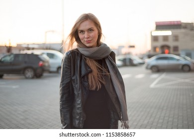 Portrait of a young woman with long hair in a jacket on the street
