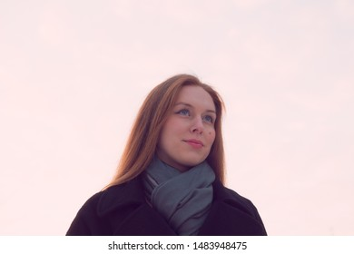 Portrait of a young woman with long hair in a coat