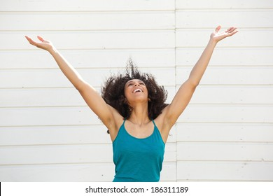 Portrait of a young woman looking up with arms outstretched