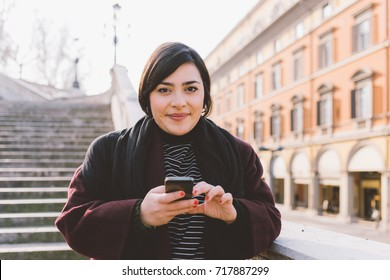 Portrait of young woman looking camera smiling, holding smart phone - technology, happiness, different beauty concept