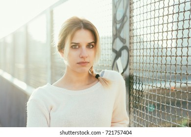 portrait of young woman looking camera back light outdoor - determination, confidence, girl power concept