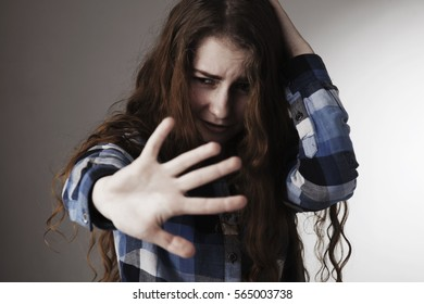 Portrait of a young woman looking in fear with her hand in front of face (Gestures, body language, psychology)