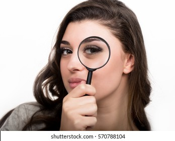 portrait of young woman looking through magnifying glass