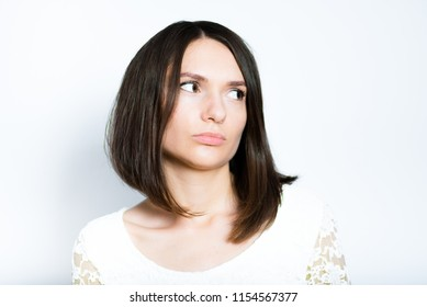 portrait of young woman looking wary, isolated studio photo on white background