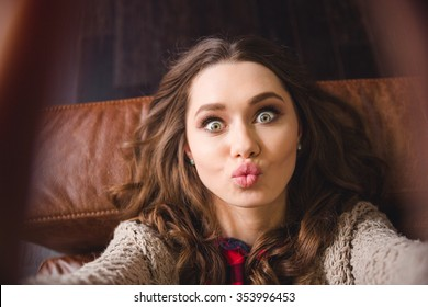 Portrait of a young woman lying on the sofa and making selfie photo while kissing at camera
