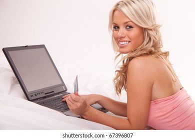 Portrait of a young woman lying on the couch and shopping from the internet using a credit card