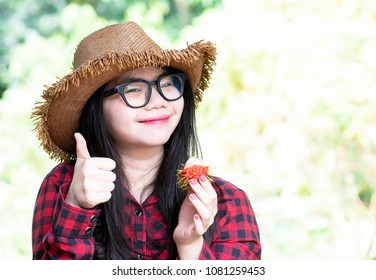 Portrait of young woman make a thump up in red plaid shirt and enjoy eating rambutan,Rambutan is a tropical fruit and sweet taste,Fresh ripe rambutans is delicious and sweet fruit for a healthy,