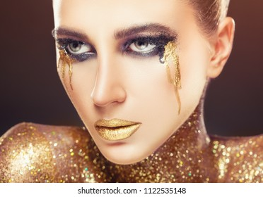 Portrait of a young woman with makeup fashion. Smokey eyes. Lips and neck are covered with sparkles