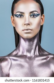 Portrait of a young woman with makeup fashion. Smokey eyes. Neck and chest are covered with metallic make-up