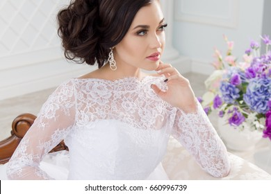 Portrait of young woman with makeup wearing earrings and lace white dress/Charming model in white dress