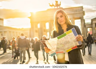 Portrait of young woman with map near Brandenburg Gate in Berlin, Germany.