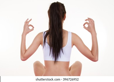 Portrait of young woman meditating in pose of lotus in isolation
