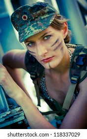 Portrait of young woman in military camouflage on the industrial background