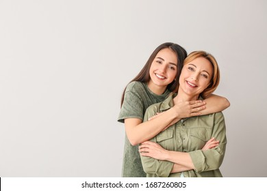 Portrait of young woman and mother on grey background
