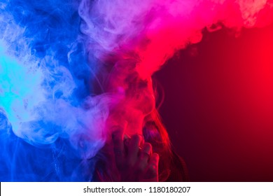 Portrait of young woman in neon red and blue smoke with vape or e-cigarettes