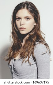 Portrait of a young woman with neutral fresh make up and casual clothes. Studio shot.