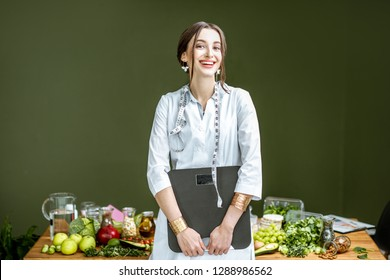 Portrait of a young woman nutritionist in medical gown standing with weights and tape measure in the office with healthy food on the background