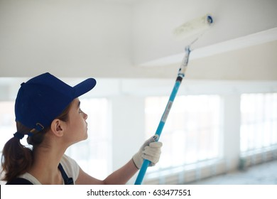 Portrait of young woman on construction site: female worker painting ceiling white using roller