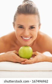 Portrait of young woman on massage table showing apple