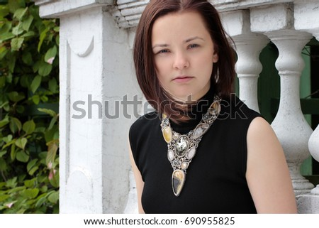 Portrait of a young woman on the street with beautiful necklace