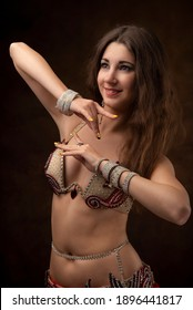Portrait of a young woman in oriental costume. Belly dance. Oriental dance. The brunette.