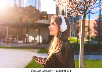 portrait young woman outdoor in the city listening music headphones - music, relaxing, enjoyment concept