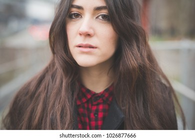 portrait young woman outdoor looking camera melancholic - assertiveness, carefree, freshness concept